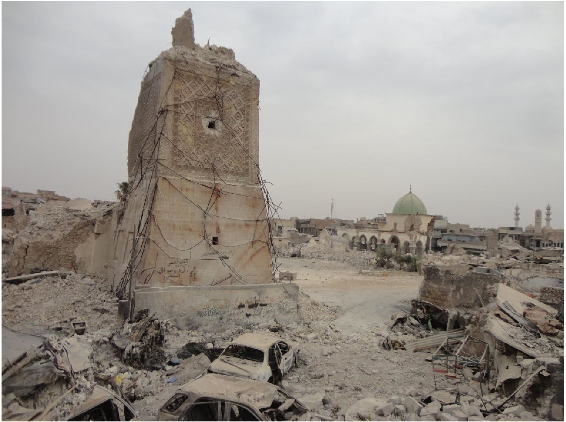 Scorched vehicles at the foot of the destroyed Al-Hadba' Minaret in Mosul, Iraq Courtesy of the World Monuments Fund