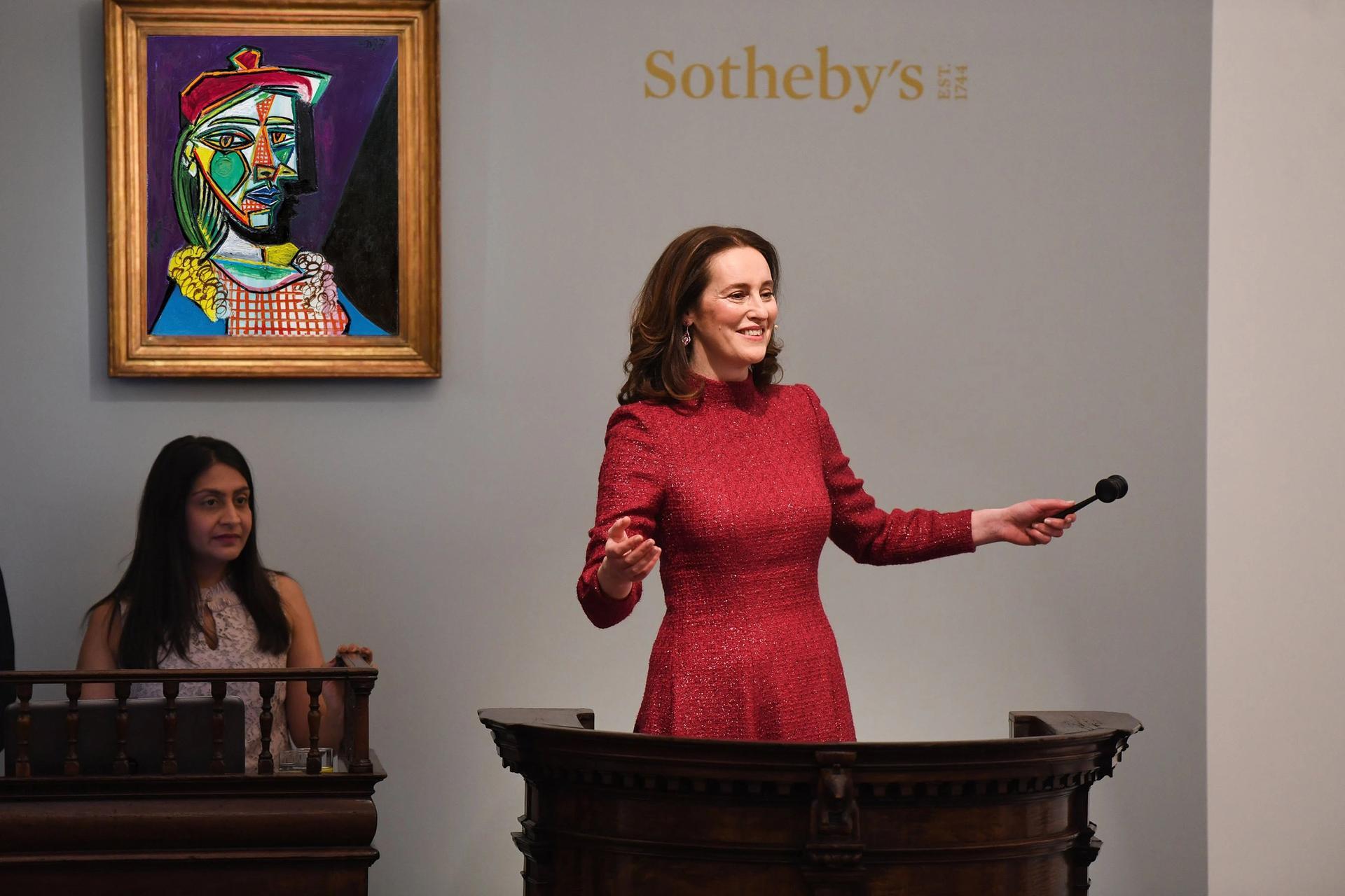Sotheby's auctioneer Helena Newman in front of Picasso's 1937 portrait, Femme au béret et à la robe quadrillée (Marie-Thérèse Walter) Sotheby's