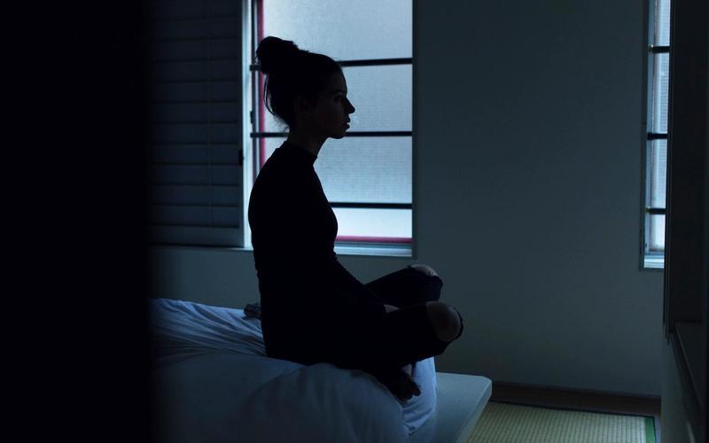 Somnioquie: Frau, auf Bett sitzend.