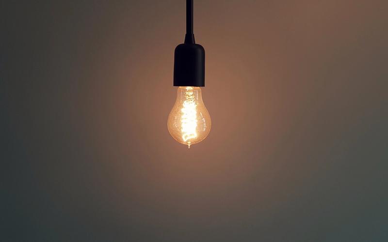 schwach leuchtende Glühbirne hängt von Decke