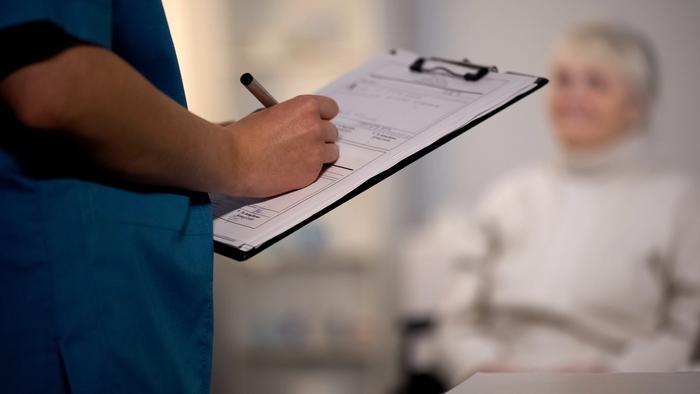 Arzt macht Notizen. Patientin im Hintergrund.