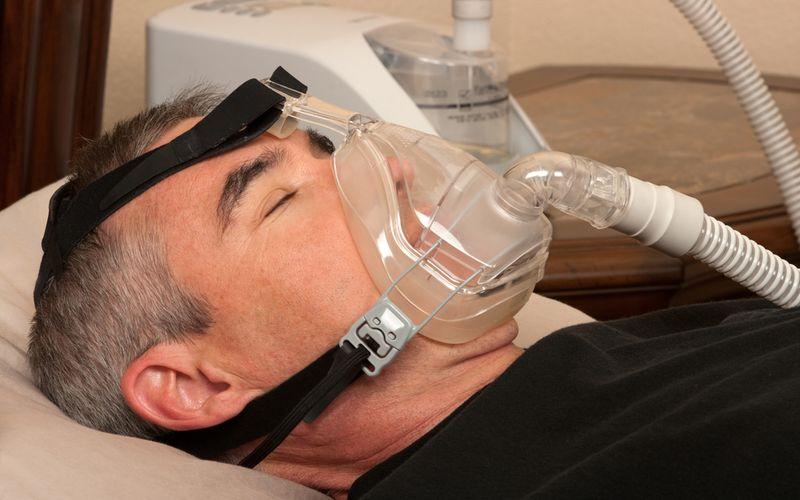 Mann mit CPAP-Maske Schlafapnoe