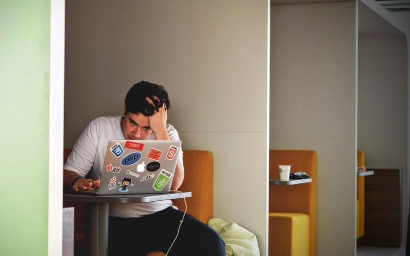 junger Mann arbeitet an Laptop