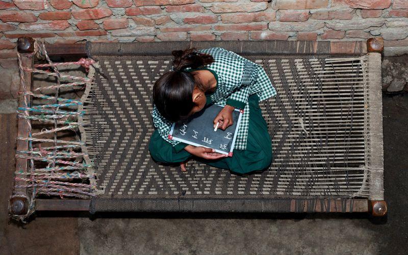 Mädchen sitzt auf Charpai Schlafkultur