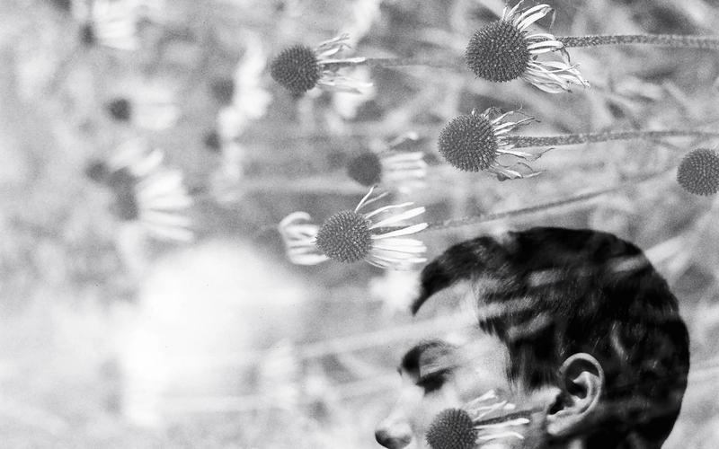 Besser einschlafen: Meditation; Frau mit geschlossenen Augen, Blumen, schwarzweiß.