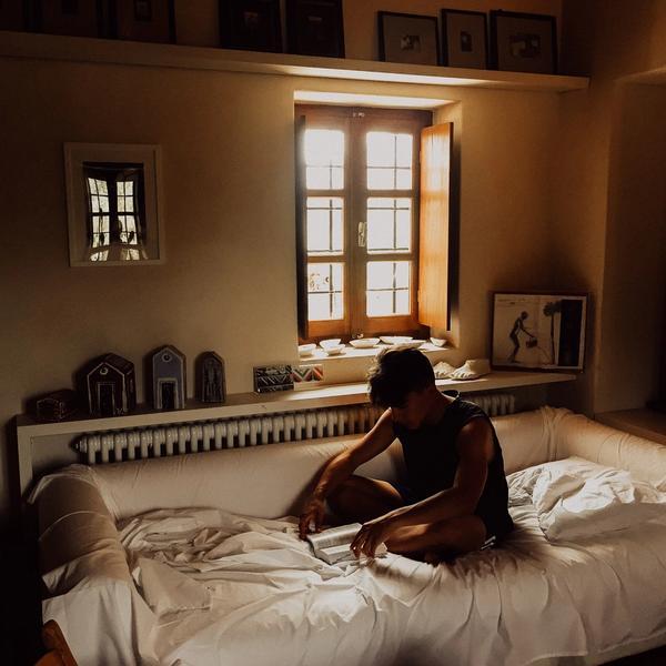 Mann sitzt auf dem Bett, liest