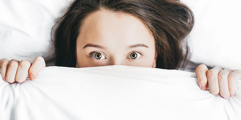 Frau Bettdecke über Mund Schlafstörungen