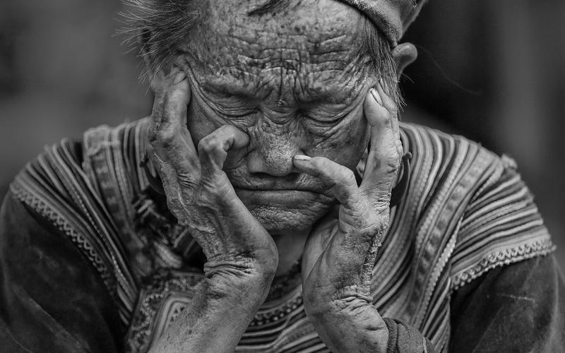 Ältee Frau stützt Gesicht auf die Hände und hat die Augen geschlossen.