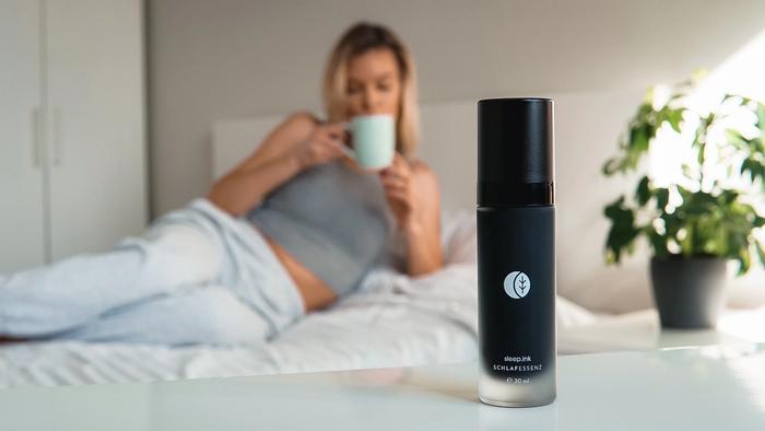 Flasche mit Schlafessenz und Frau mit Tasse auf einem Bett im Hintergrund