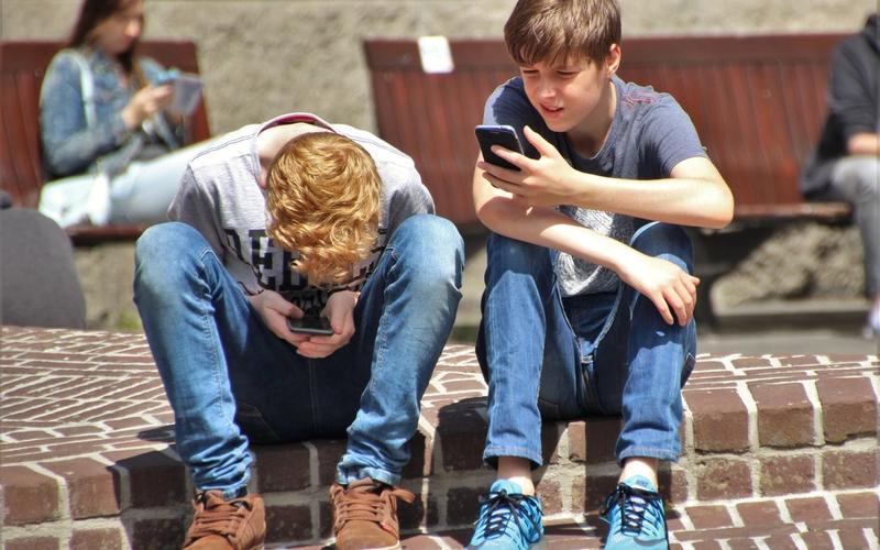 Jugendliche, die mit ihrem Smartphone beschäftigt sind.