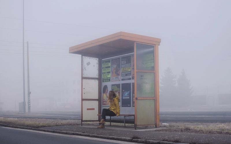 Frau an Bushaltestelle