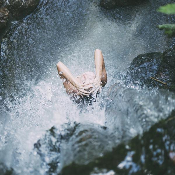 Frau steht unter einem Wasserfall