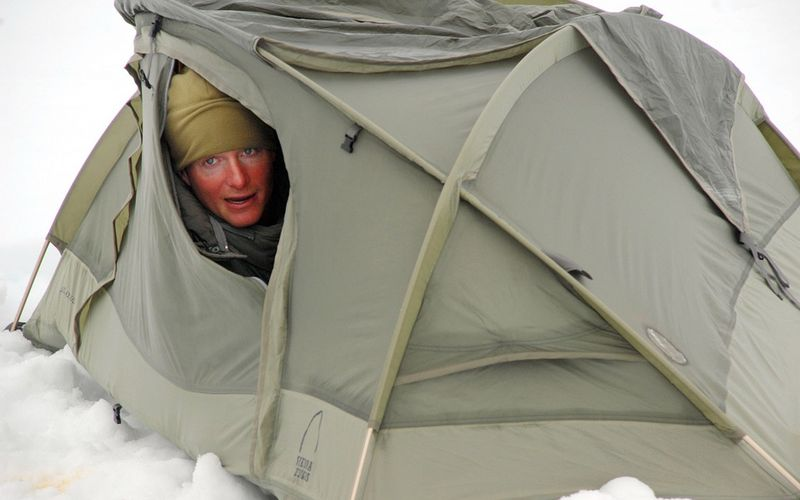 Zelt im Schnee, frierender Mann