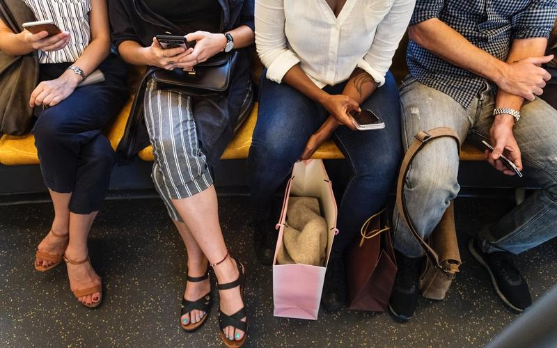 Eine Reihe Menschen mit Smartphones in der Hand.