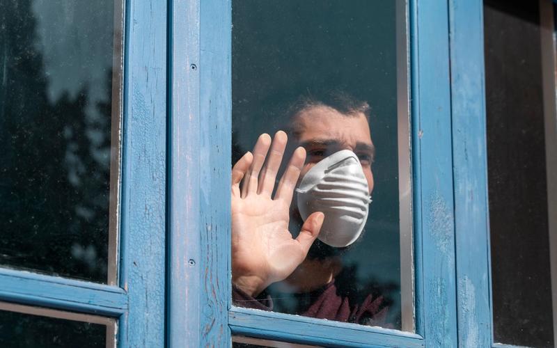 Mann mit Maske in Quarantäne schaut aus dem Fenster