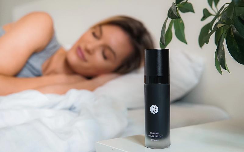 Glasflasche mit der Schlafessenz und schlafende Frau im Hintergrung