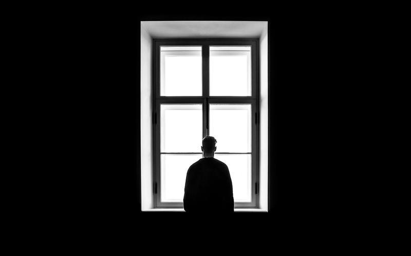 Mann vor Fenster: Einsamkeit und Schlaf