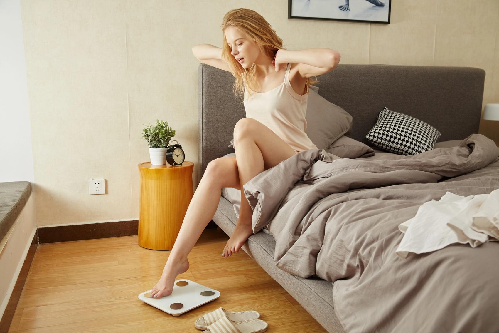 Schlaf dich schlank Frau auf Bett und Waage