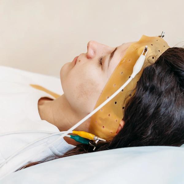 Lernen im Schlaf; Frau auf Bett mit EEG