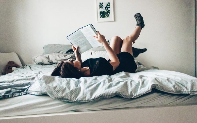 Frau lernt und liegt auf dem Bett
