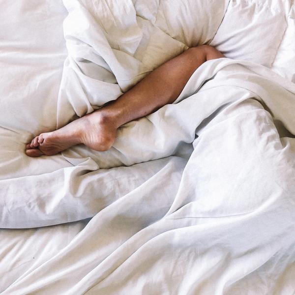 Mensch im Bett mit weißen Laken