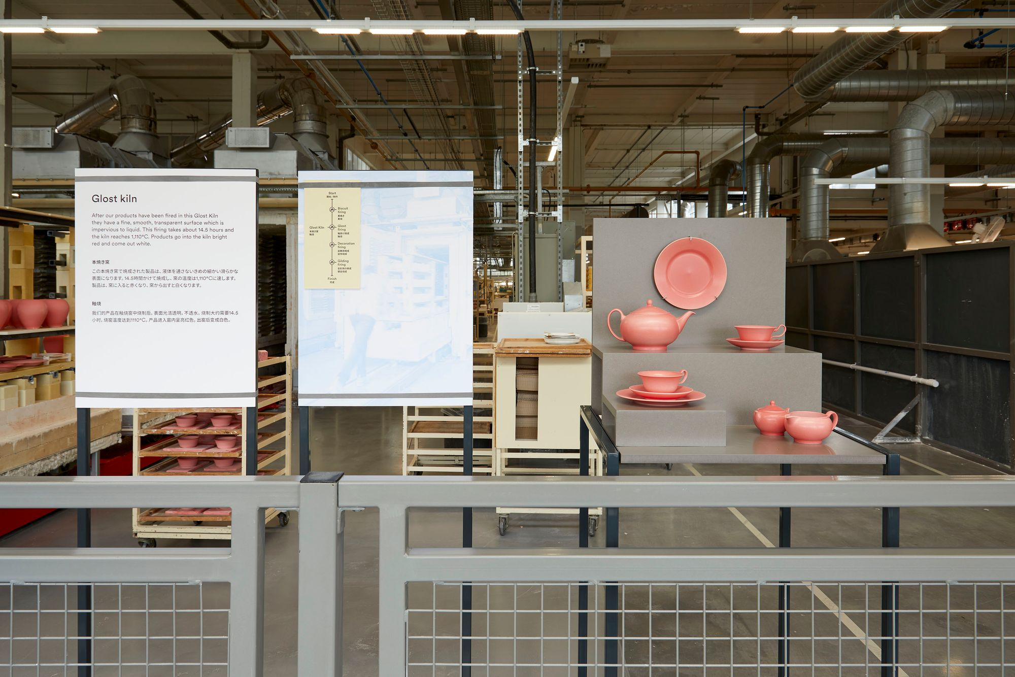 Display furniture and interpretation panels on factory floor showing a set of crockery sprayed with glaze ready to go in the kiln