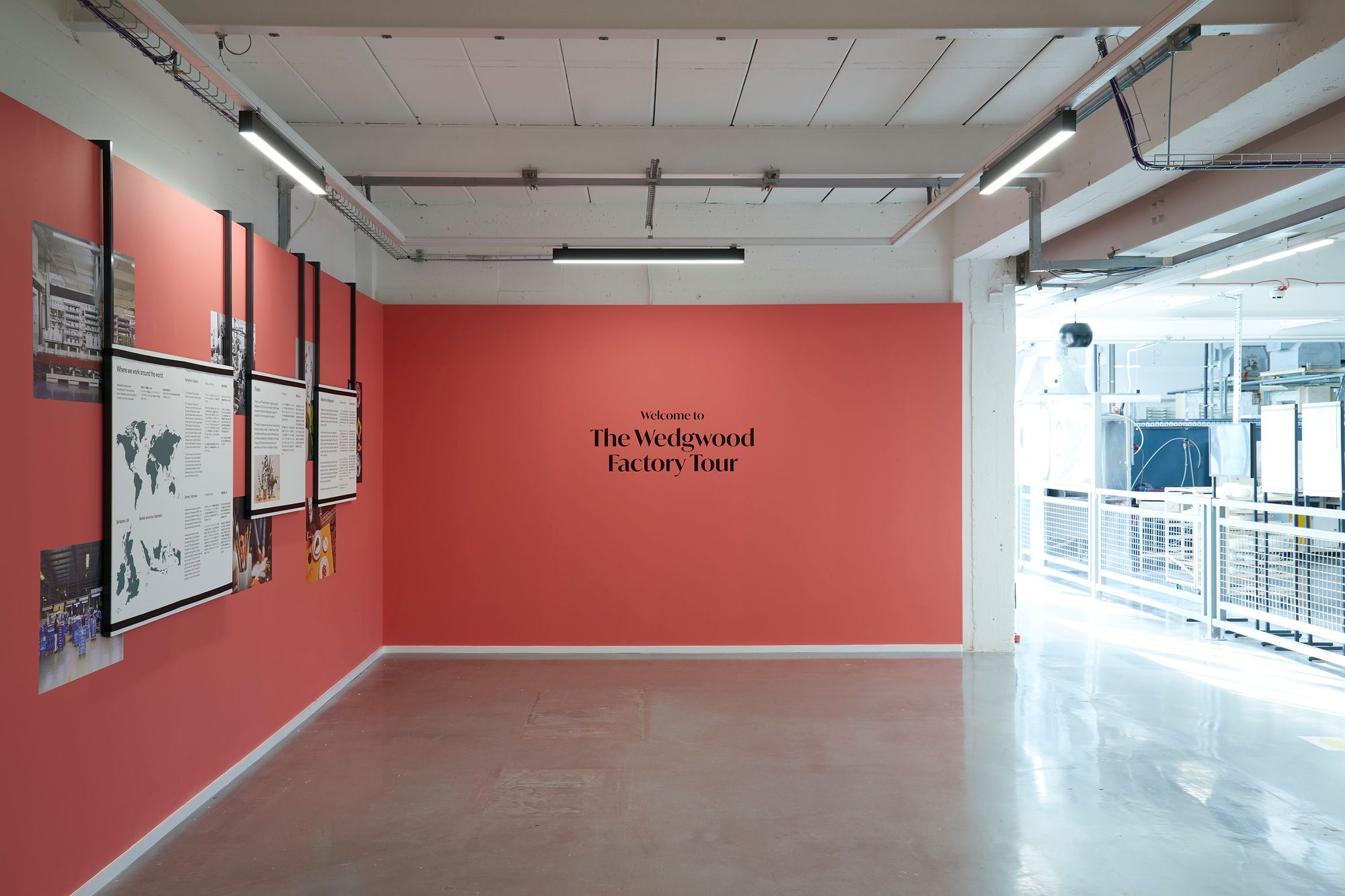 Factory introduction space, title vinyl on red wall and text panels mounted on frames hanging from the ceiling