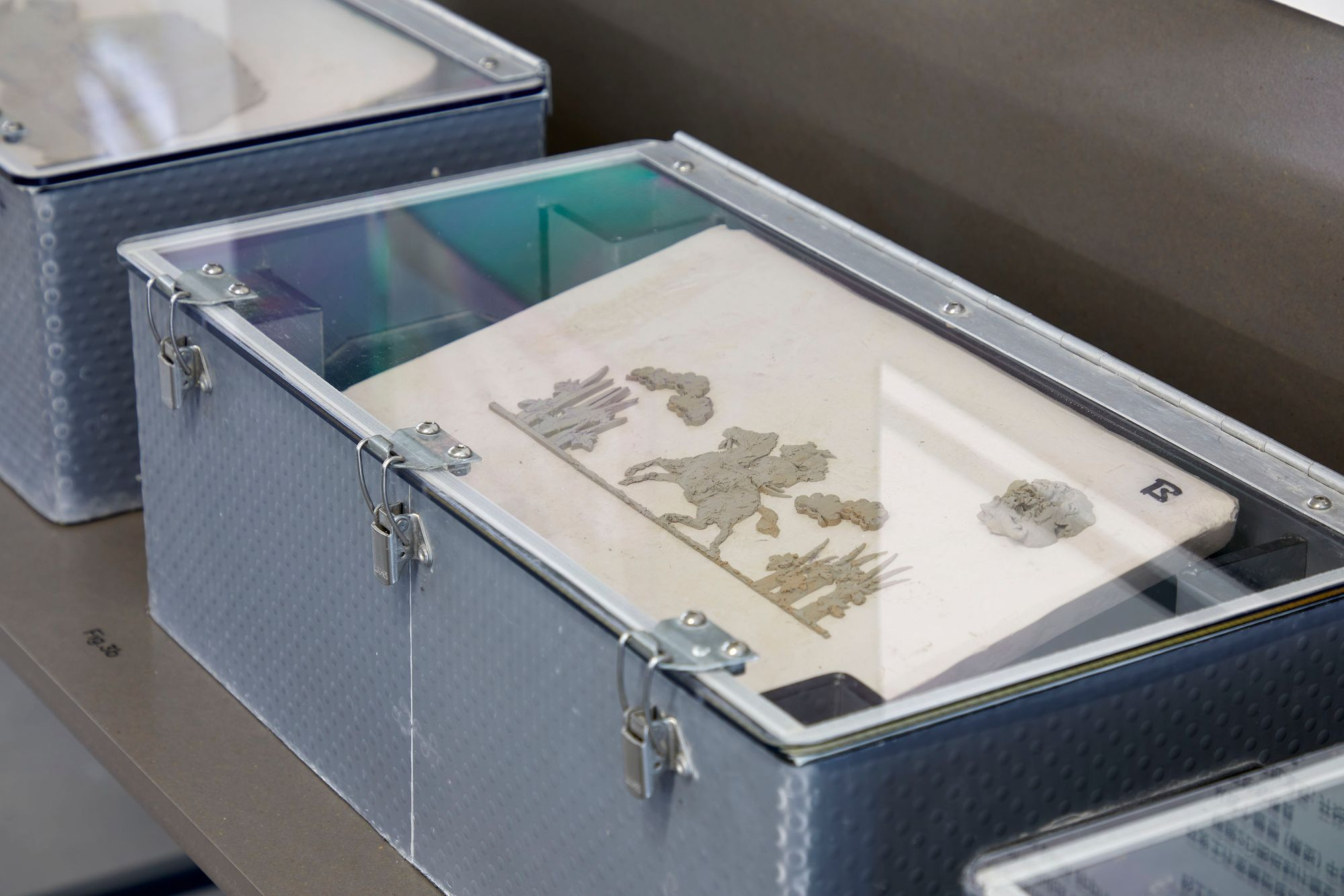 Box with clear perspex lid showing the process of creating reliefs to be applied to ceramic products.