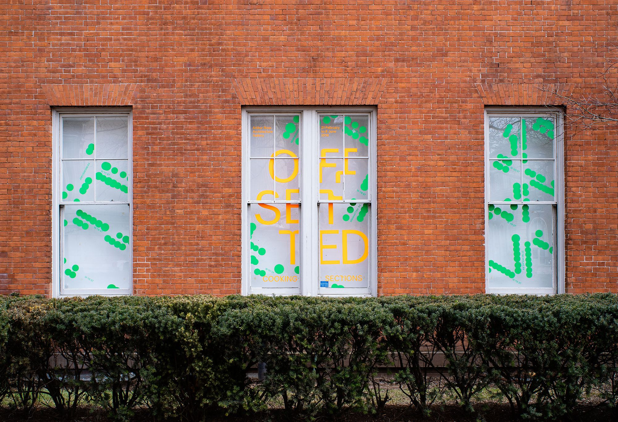 Photograph of window vinyl on exterior of gallery. 'Offsetted' is in fluorescent orange cut vinyl and surrounded by green cut vinyl dots.