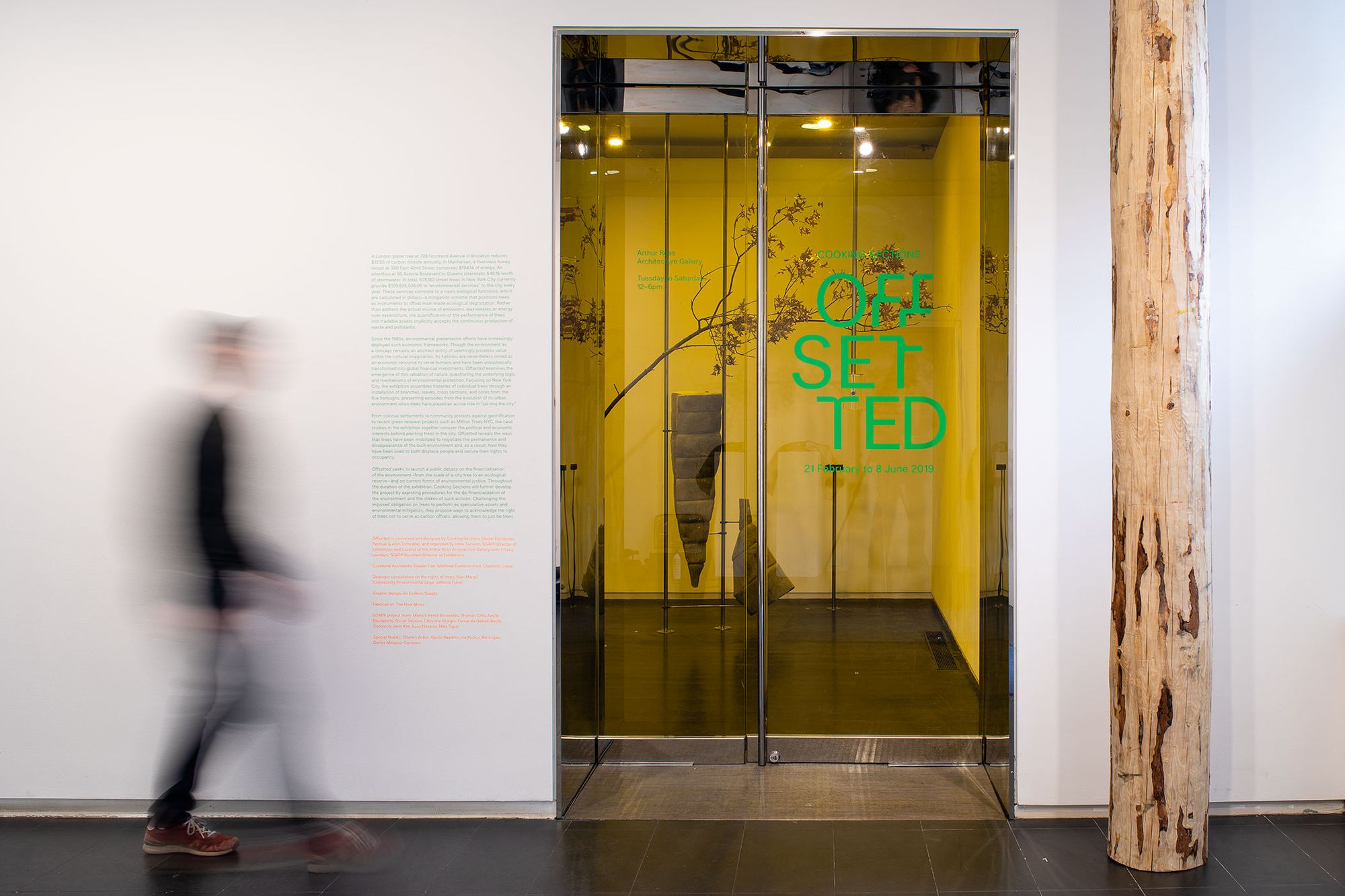 Photograph of interior exhibition vinyl. The title 'Offsetted' in green cut vinyl on glass door to gallery and green interpretation text on a white wall next to the door.