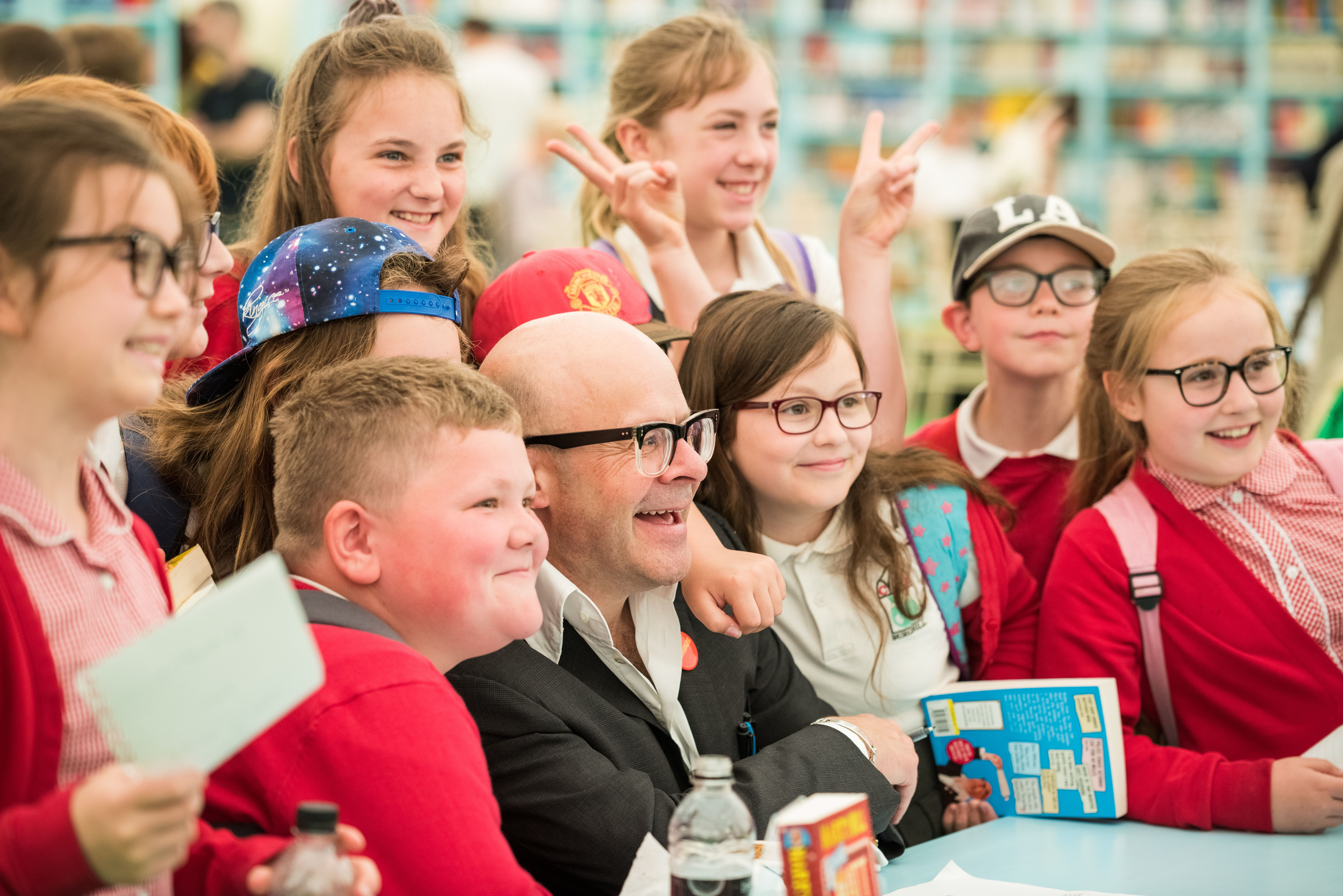 Image shows Harry Hill surrounded by school children.
