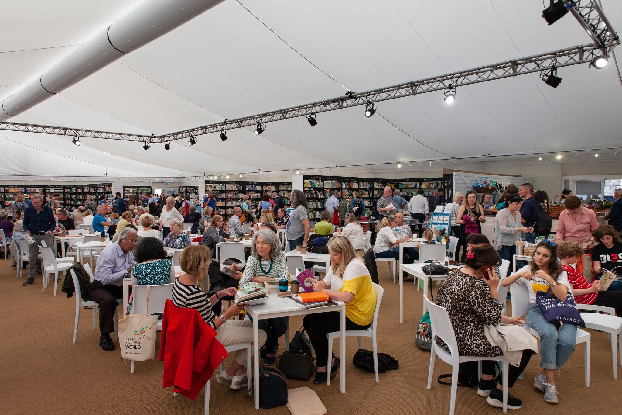 Photo shows people sat at tables in a bookshop cafe