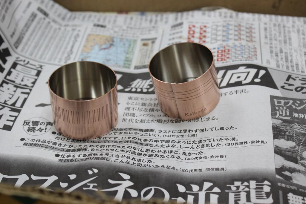 Kaikado sake cups in brass on Japanese newspaper in Kyoto