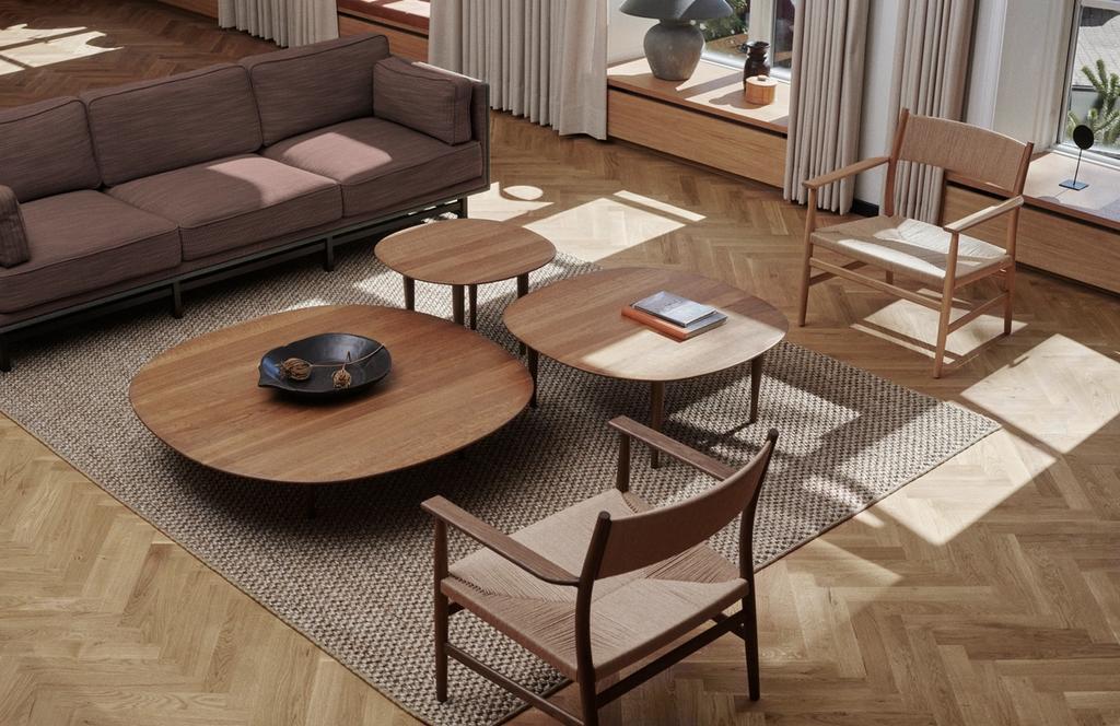 Low sofa tables in smoked oak on sisal carpet and herringbone wooden floor