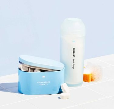 Blueland Dish Duo on white tile: 1 refillable silicone shaker and Powder Dish Soap, 1 refillable tin and dishwasher tablets