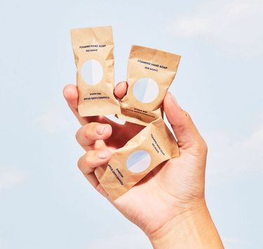 Hand holding 3 Blueland Foaming Hand Soap tablets in compostable wrappers against the sky