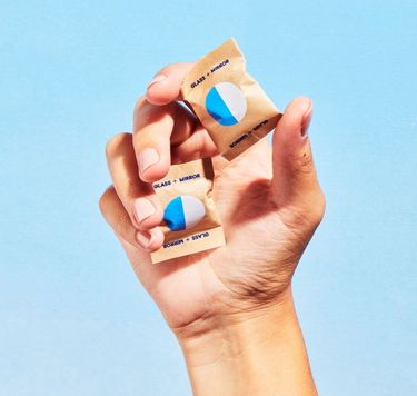 Hand holding two Blueland Glass + Mirror refill tablets in compostable wrappers against blue background