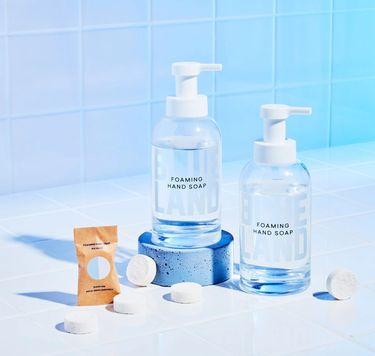 Blueland Hand Soap Duo against tile: 2 refillable glass  bottles, 5 unwrapped Foaming Hand Soap Tablets, 1 wrapped tablet