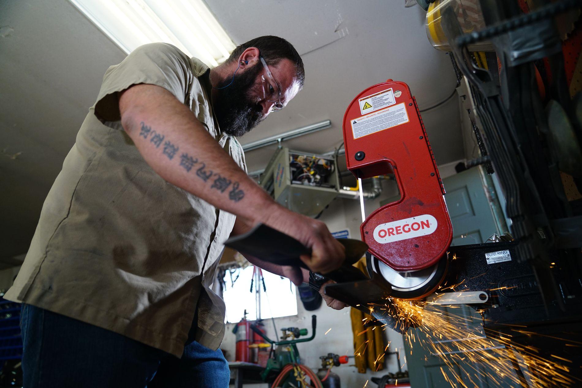 Mechanic sharpening mower blades