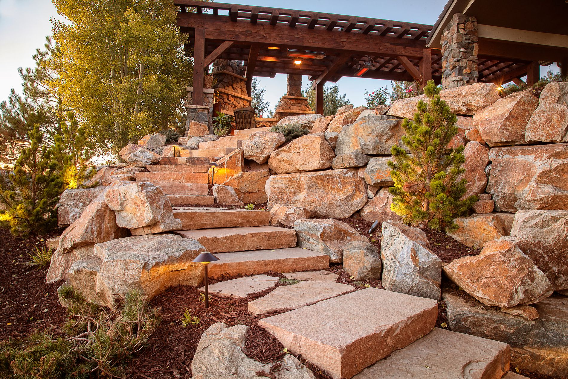 Sandstone slab staircase with boulder retaining wall and landscape lighting