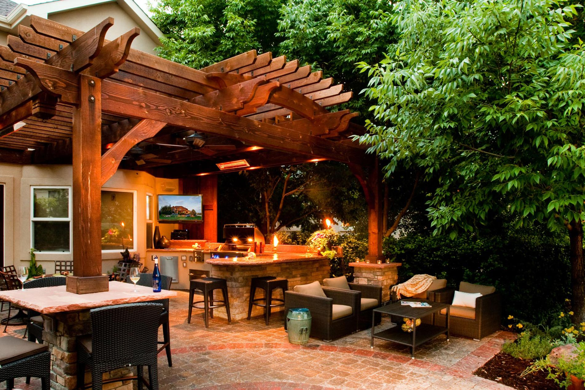 Outdoor Kitchen With Paver Patio and Shade Structure at Night