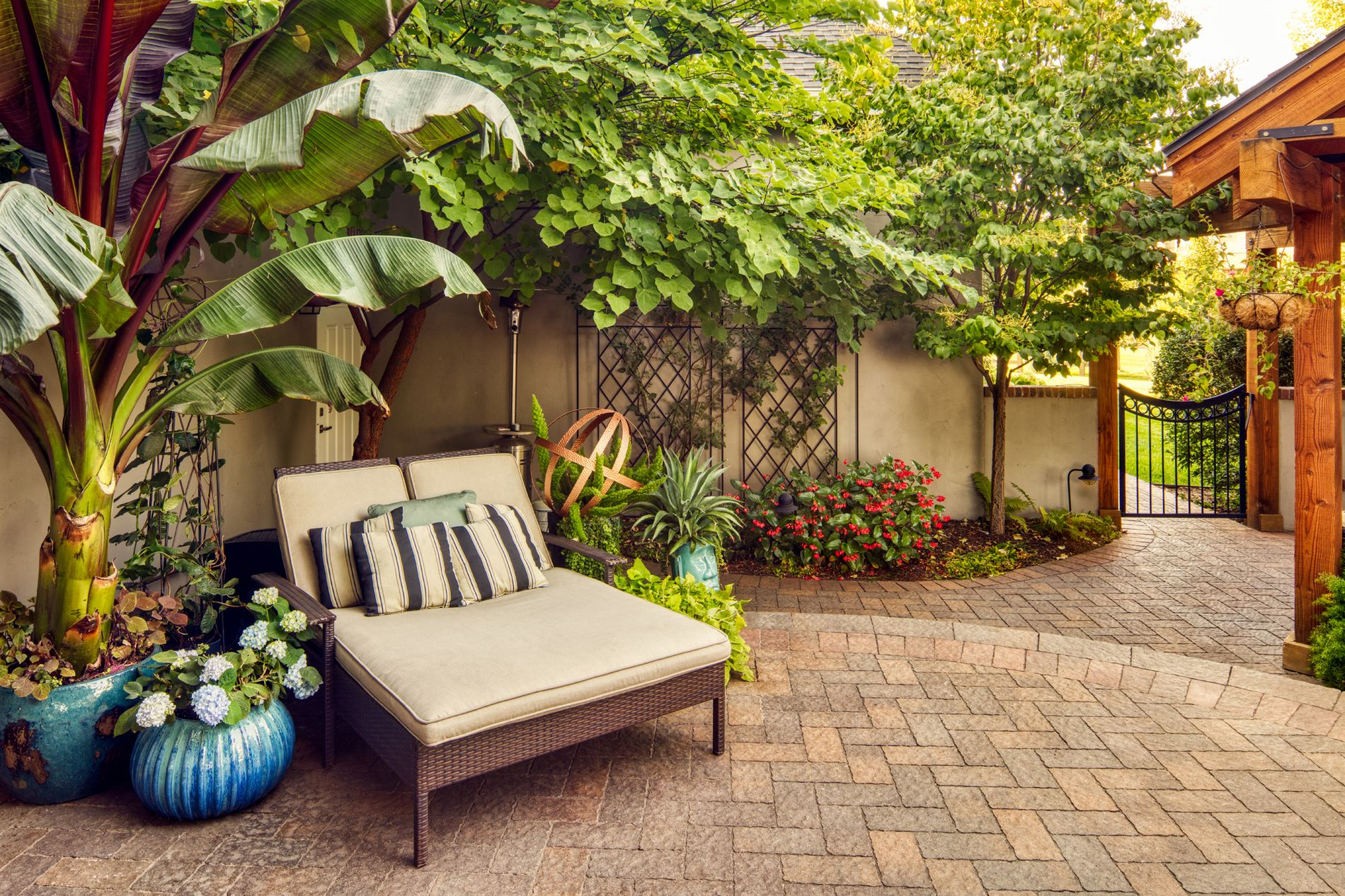 Paver patio and lounge chair in backyard courtyard