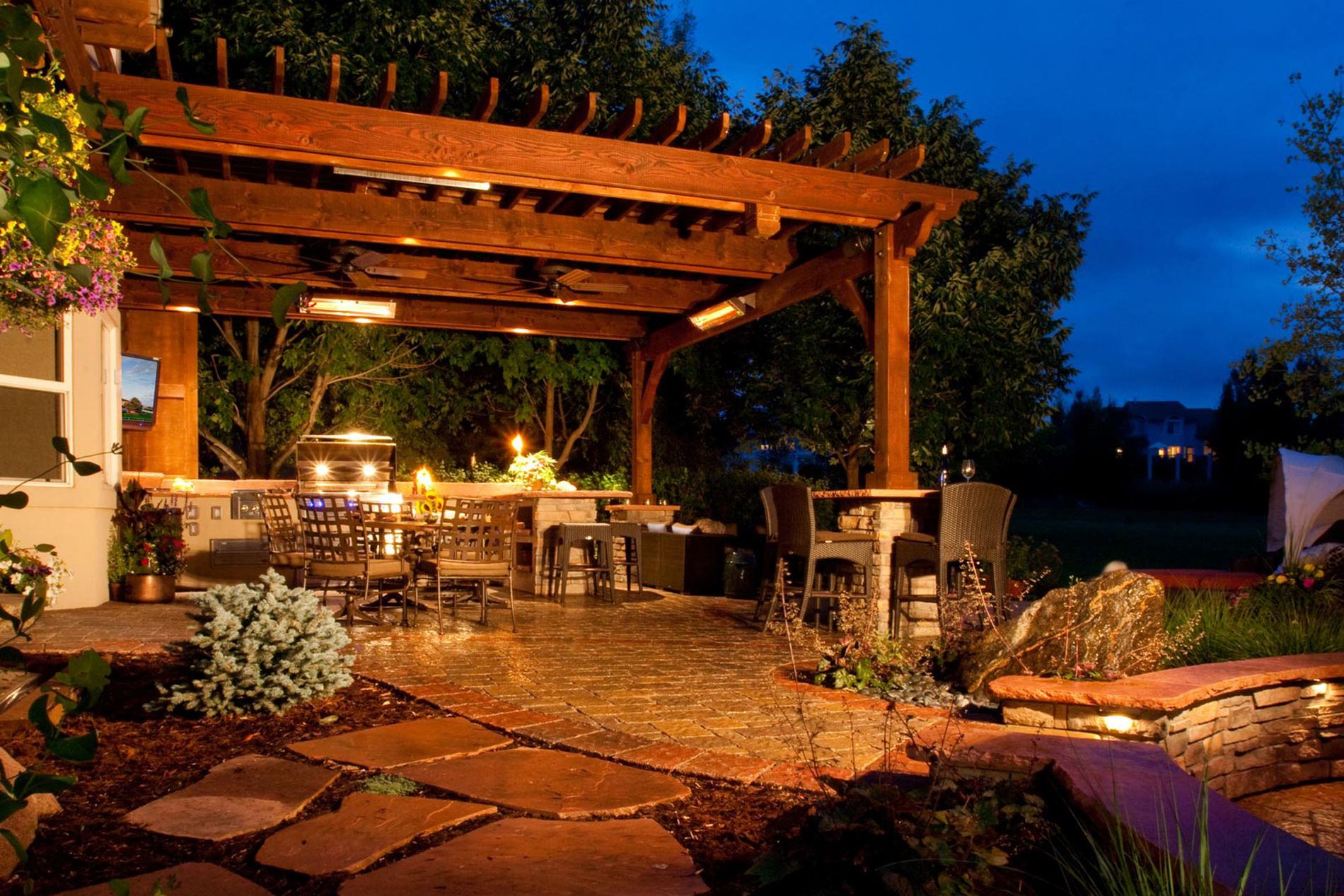 Outdoor Kitchen With Paver Patio and Shade Structure with Landscape Lighting