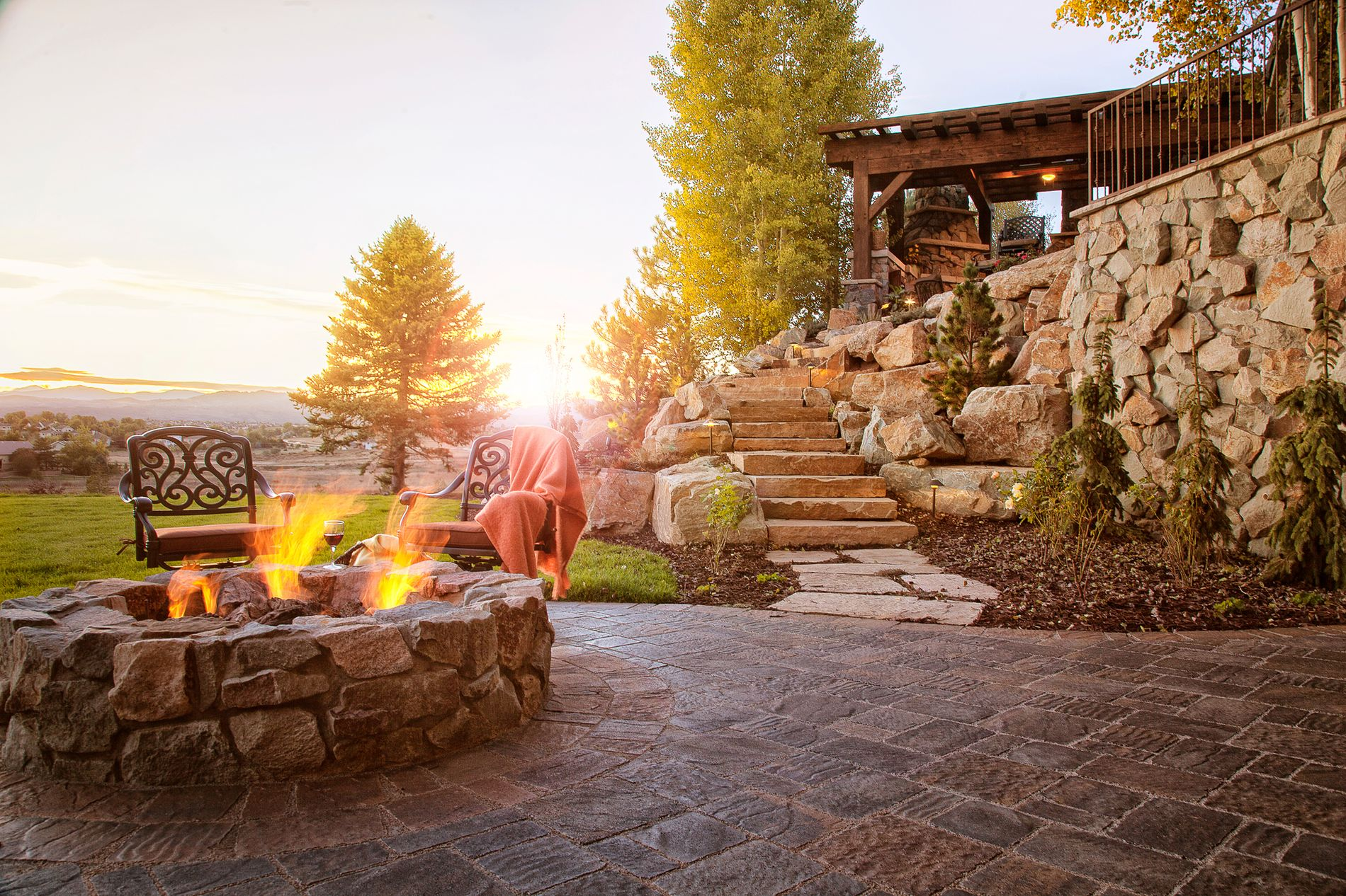Fire pit and sandstone slab staircase and retaining wall with paver patio