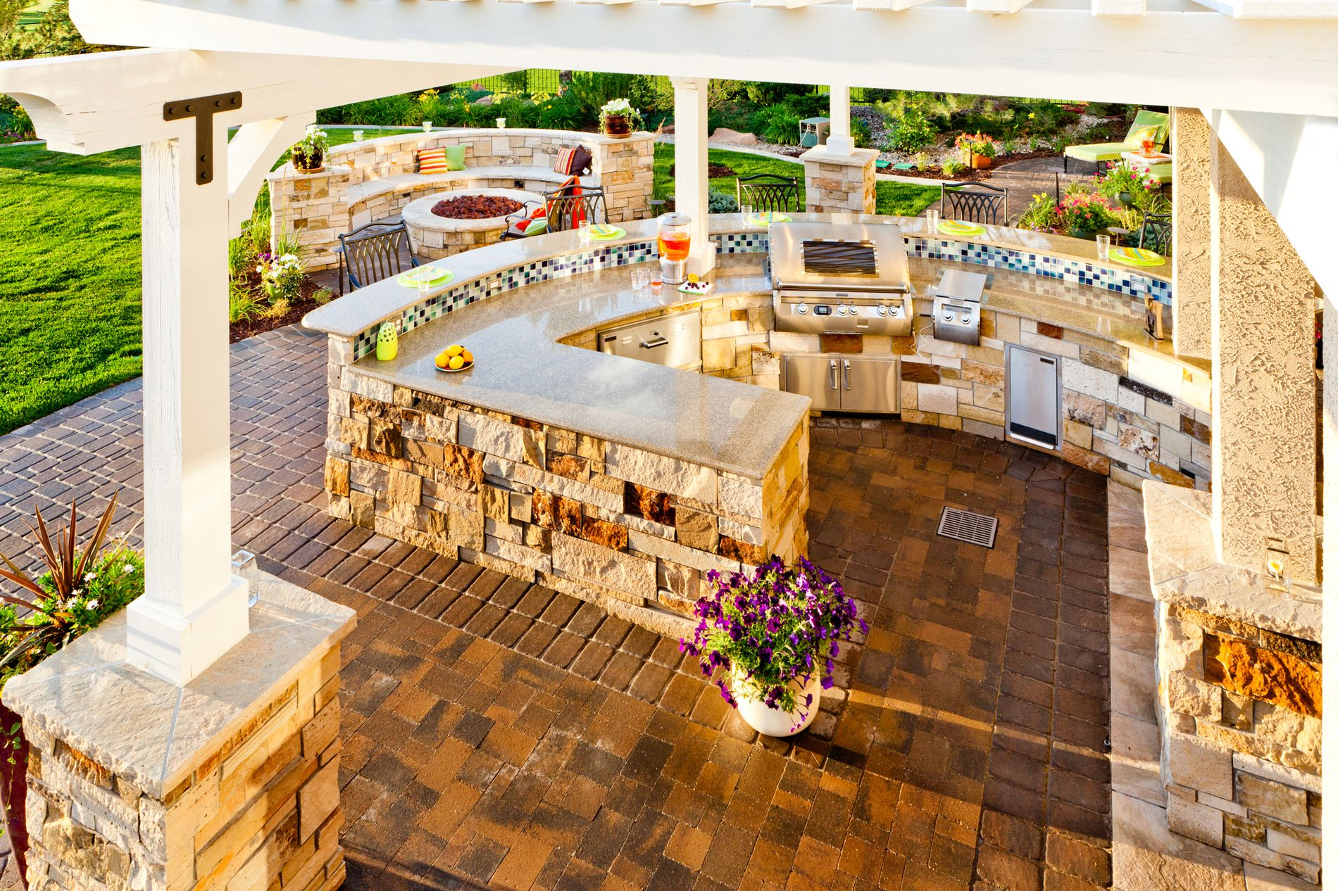 Outdoor Kitchen with White Pergola and Paver Patio
