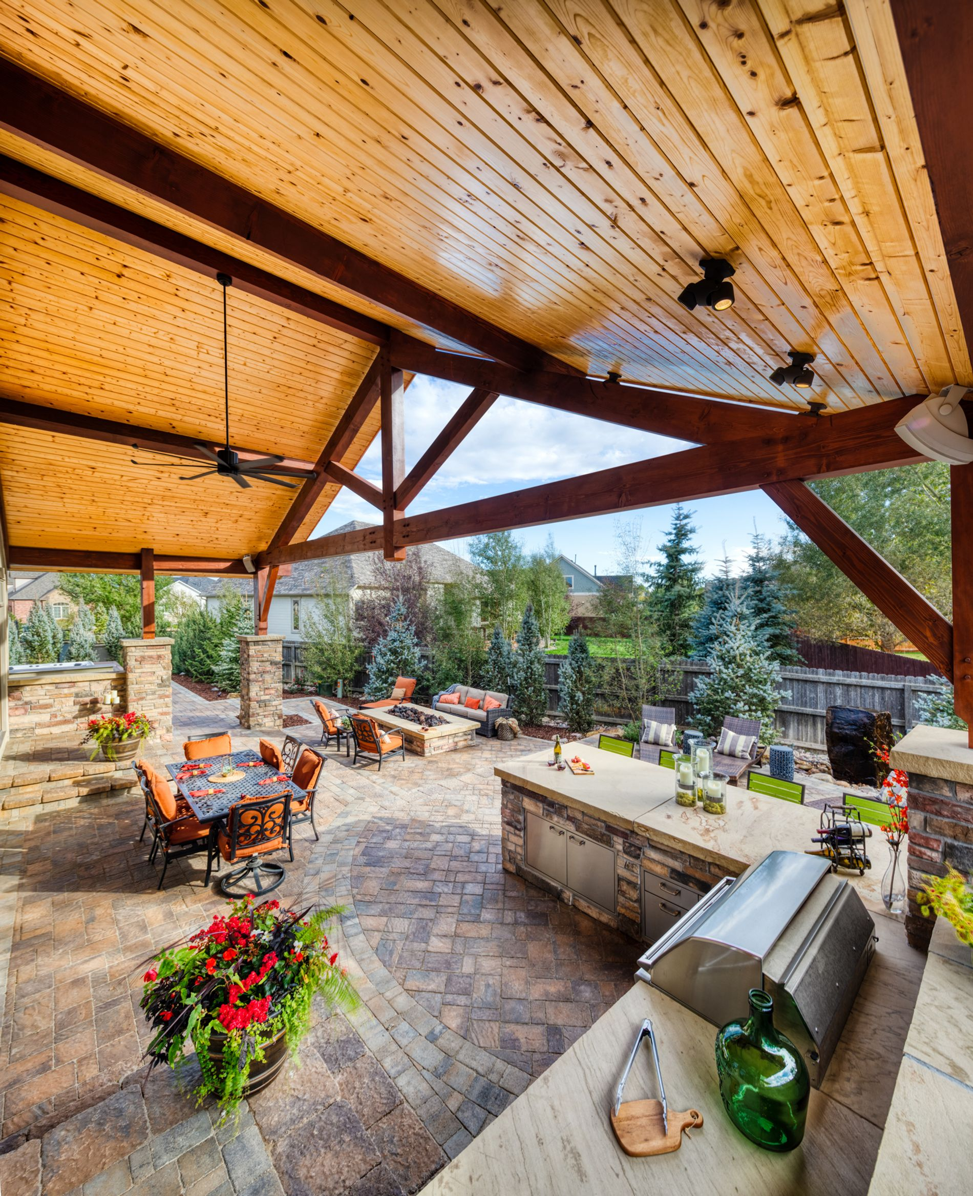 Timber frame gable roof with tongue and groove ceiling covers a paver patio