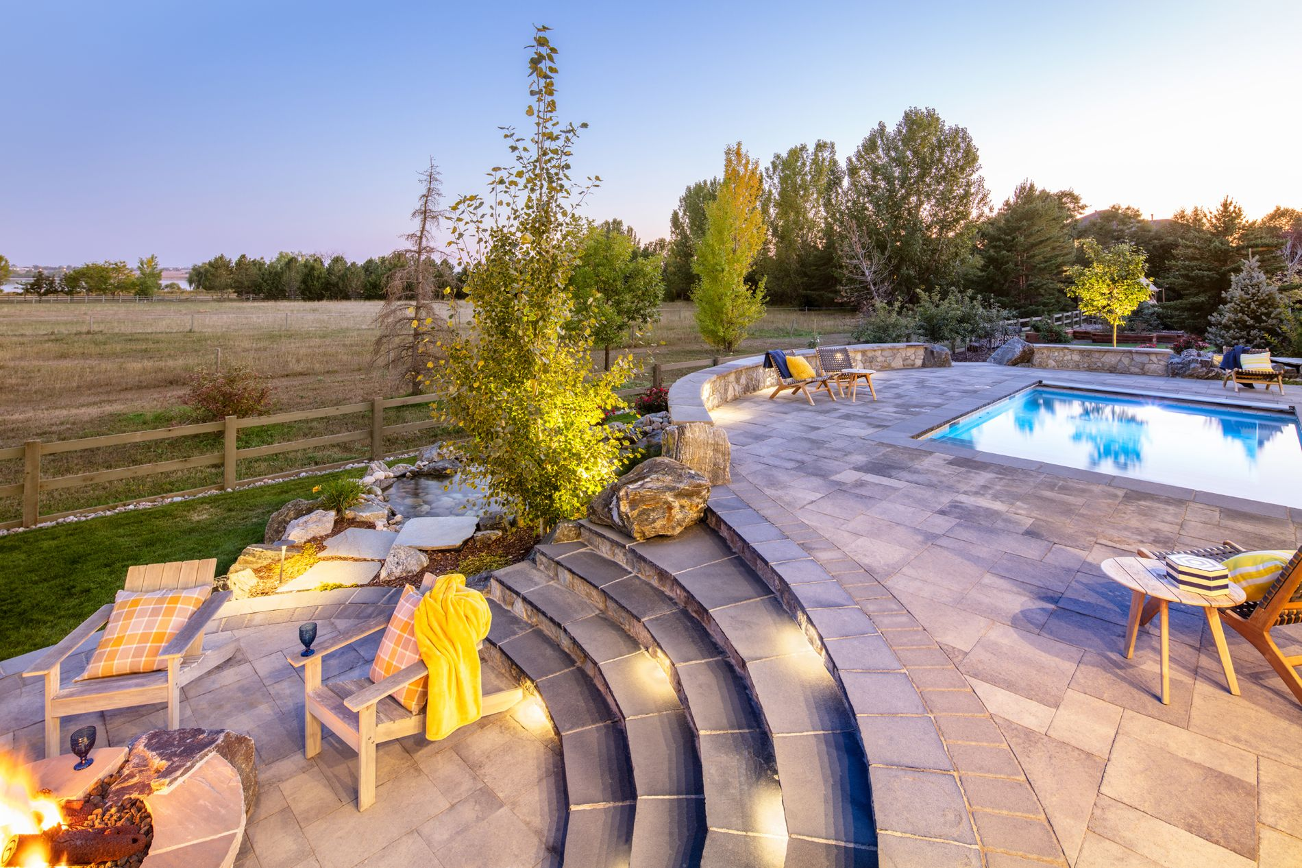 Swimming pool with paver patio and stairs leading to fire pit