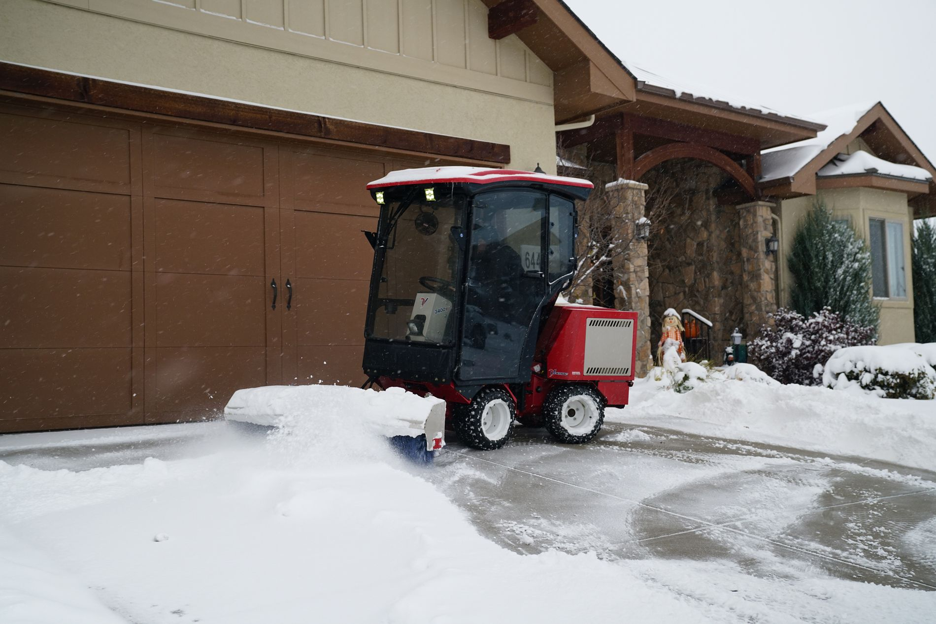 Ventrac machine with snow broom clearing snow on driveway