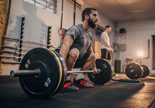 man setting up for barbell deadlift | sprinting tips