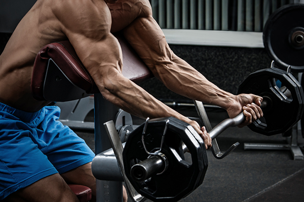 man doing preacher curl   how to get more vascular